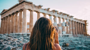 Woman standing in front of ancient building in Athens, Greece