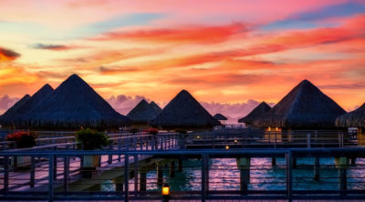 Scenery of bungalows in Bora Bora with beautiful orange & purple sunset