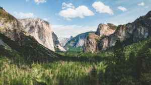 birds eye view picture of yosemite in california - green valley below with huge glacier peaks on both sides