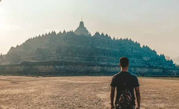 Man walking towards ancient temple - Borobudur Temple, Magelang, Indonesia